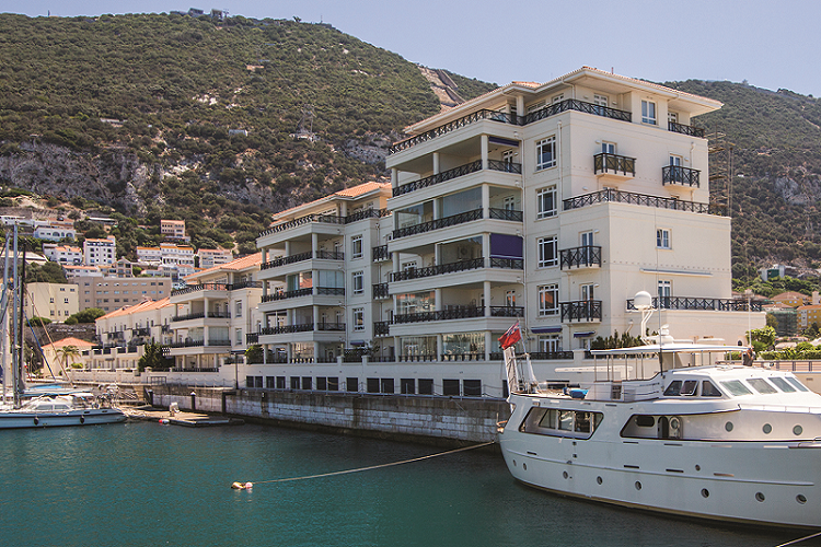 Luxury homes on the edge of a marina where yacht are moored